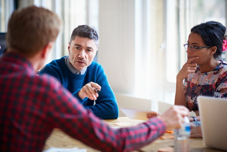 two men and woman talking around table