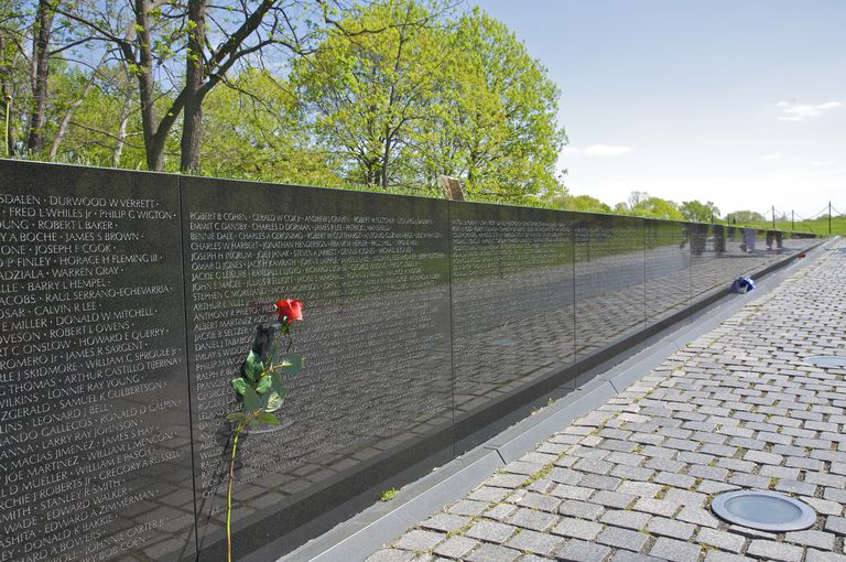Single long-stemmed red rose left atop names inscribed in Vietnam Veteran's Memorial, Washington DC, USA