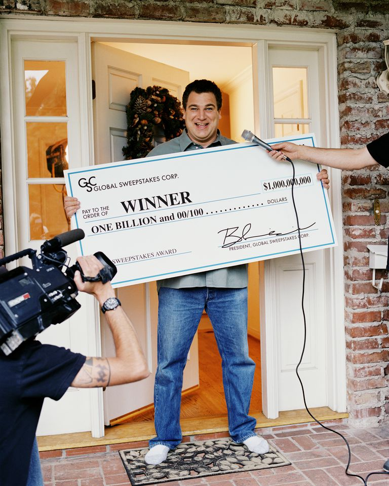 Man receiving one billion dollar check, interviewed by television crew