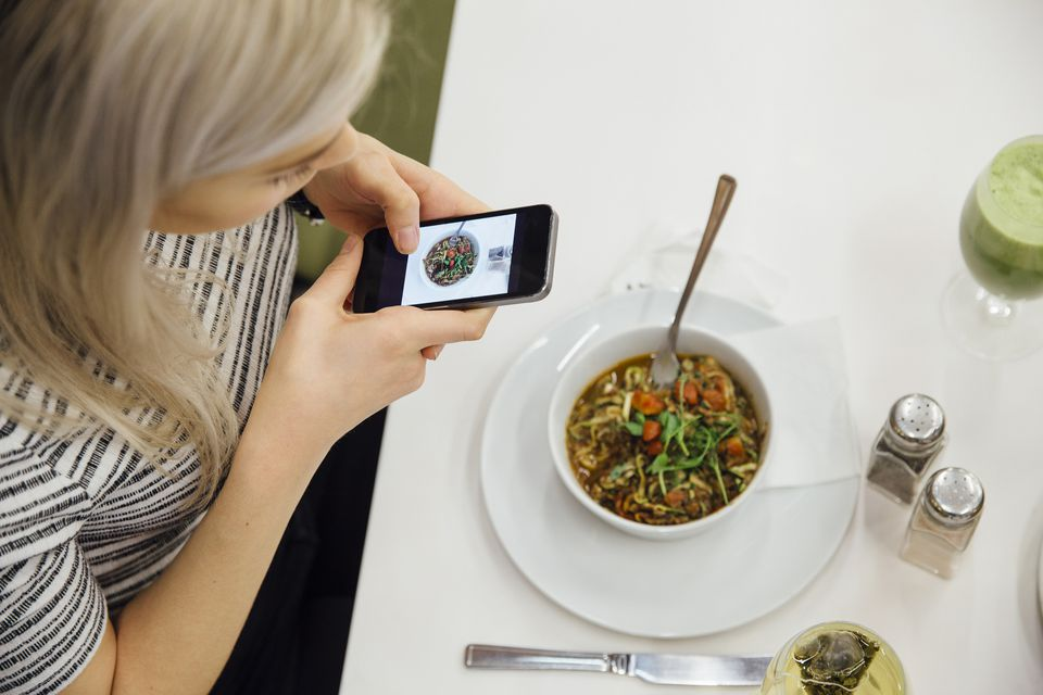 Taking a photo of her vegan meal.