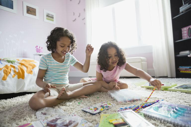 Sisters doing crafts in bedroom