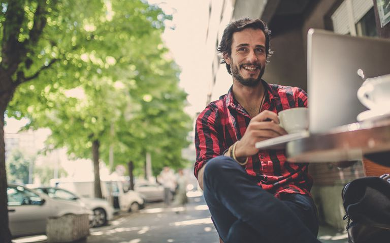 Man drinking coffee in an outdoor cafe browsing the internet.