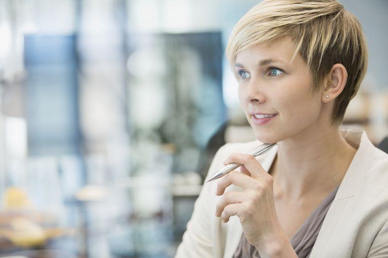 Pensive businesswoman holding pen