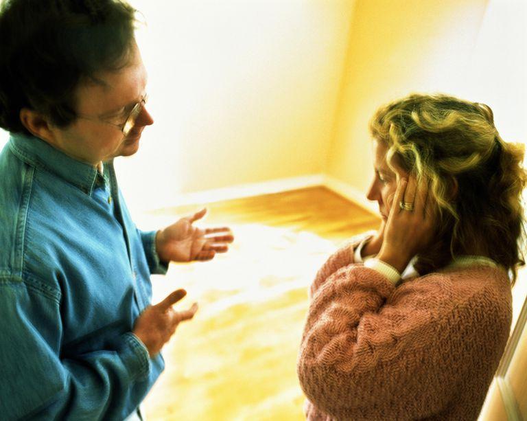 Couple talking in empty room, woman covering ears