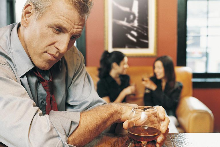 Portrait of a Drunk Businessman Leaning on a Bar Counter With Business People in the Background