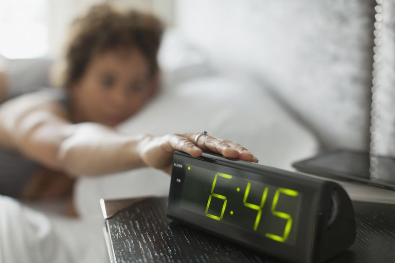 Woman reaching for snooze button