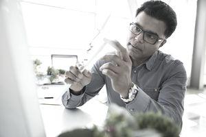 Serious scientist examining wind turbine model in laboratory