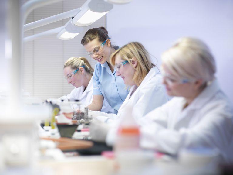 Professional dentist teaching apprentices in dental laboratory