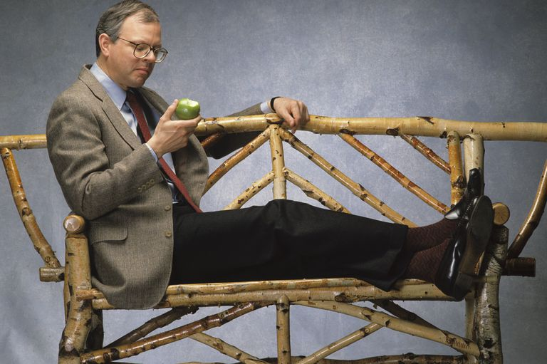 suited professional man with glasses eating a green apple while reclining on a rustic stick and twig long wooden bench