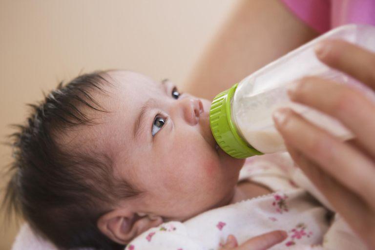Mother feeding newborn baby daughter