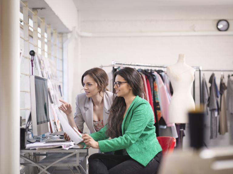 Fashion designers working at computer in fashion design studio