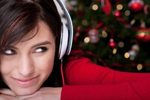 A woman listening to Christmas music on her headphones.