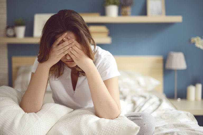 woman suffering from migraine in bed
