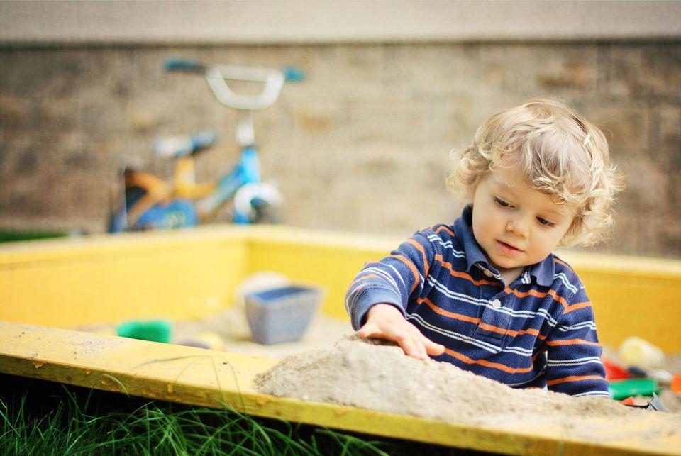 Child playing in sandbox.