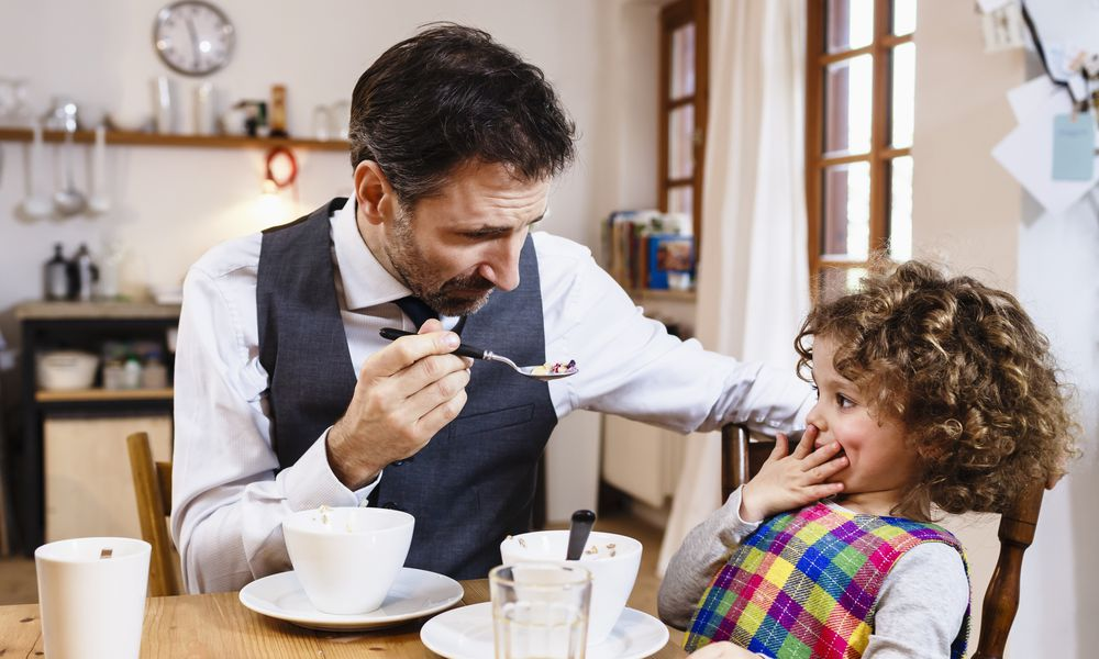 Man feeding reluctant child