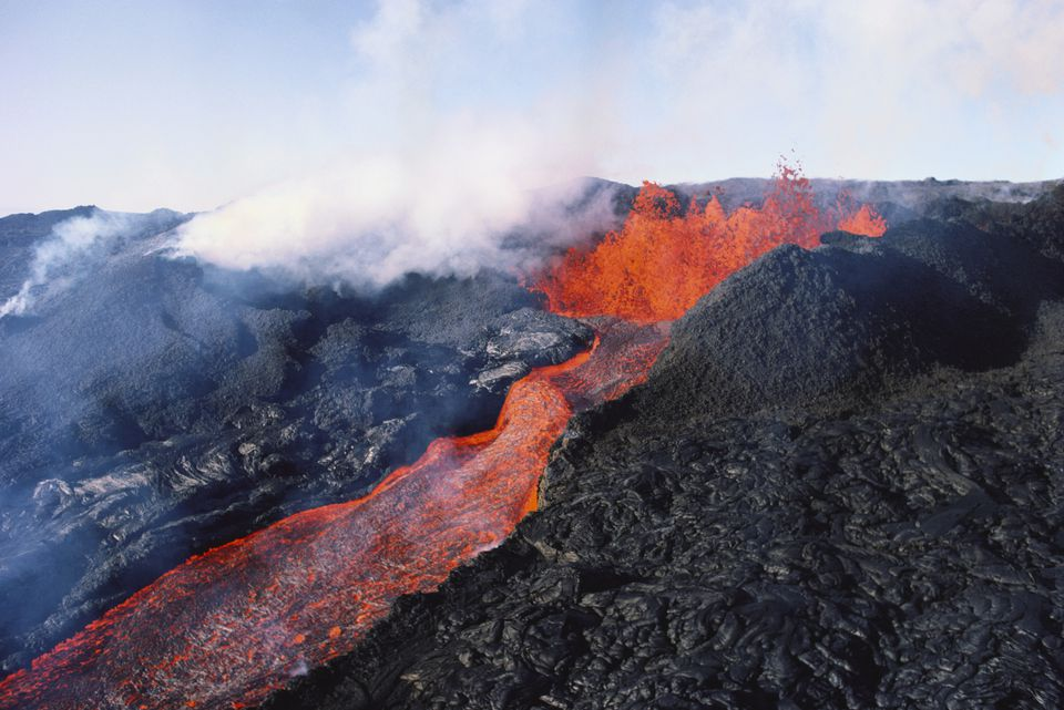 Mauna Loa volcano eruption, with lava flow and steam rising