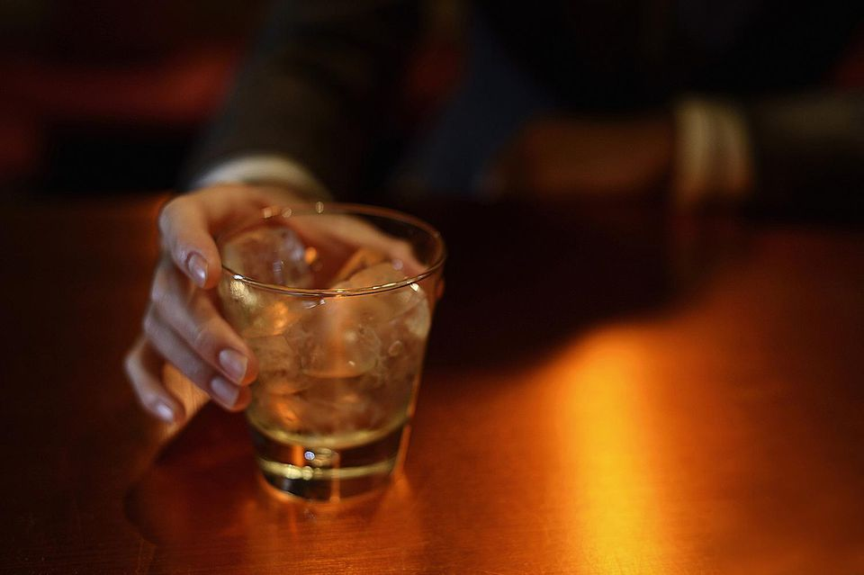 Man holding a whiskey on the rocks in a bar.