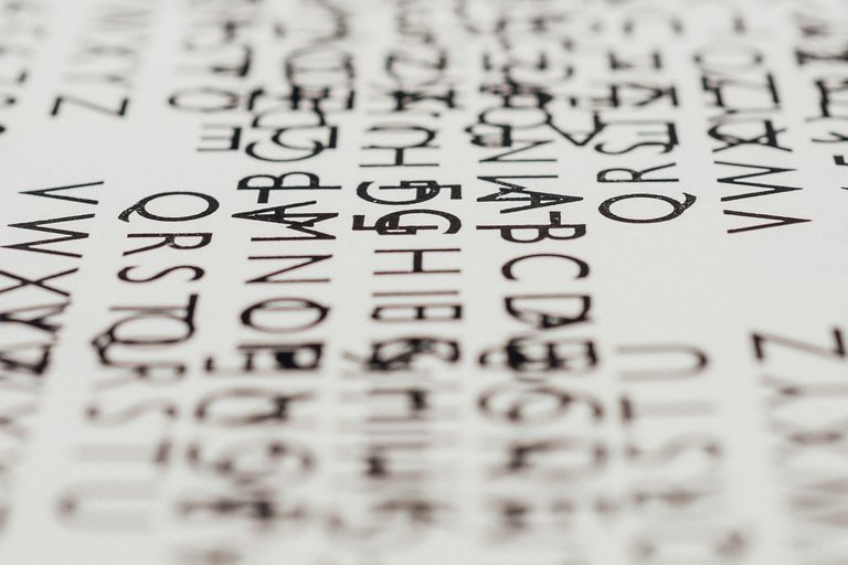 Picture of random black, overlapping text on a white sheet of paper