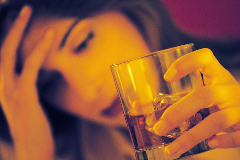 Stressed woman holding alcoholic drink