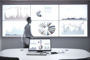 Businessman walking past a display of charts and data
