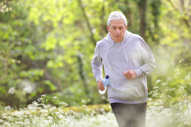 Older man running through woodland and flowers