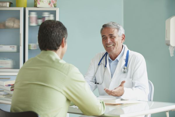 Doctor Speaking To Patient In Office