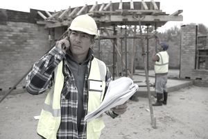 Builder using phone on construction site