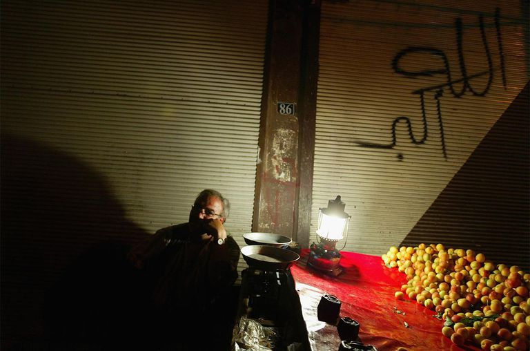 A man sells fruits past midnight under a graffiti saying 'Allahu Akbar -god is Great'