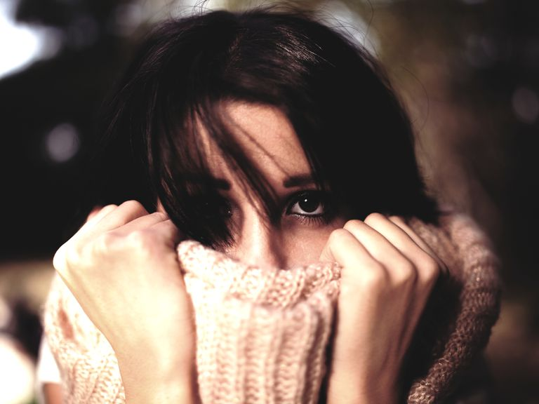 Woman pulling sweater over face