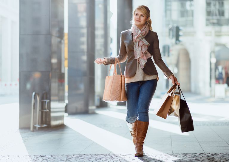 petite woman walking with shopping bags