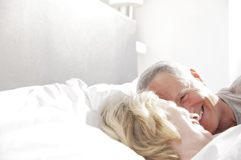 Senior couple laughing in bed