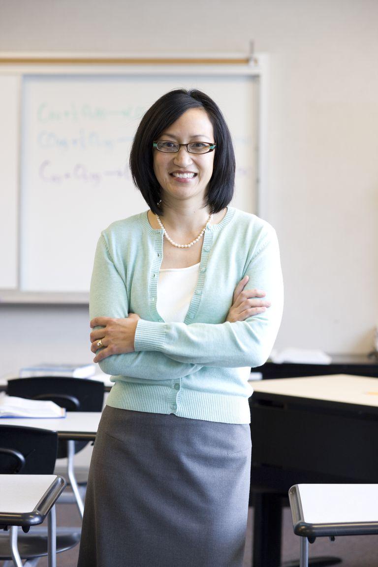 Teacher smiling in classroom, portrait