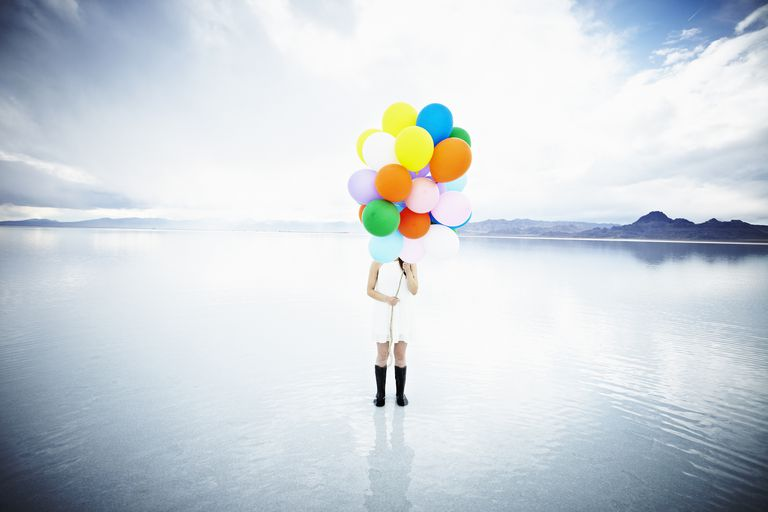 Woman in dream holding colorful balloons and standing on water