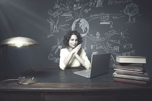 Young female teacher sitting behind desk with blackboard covered in environmental themes