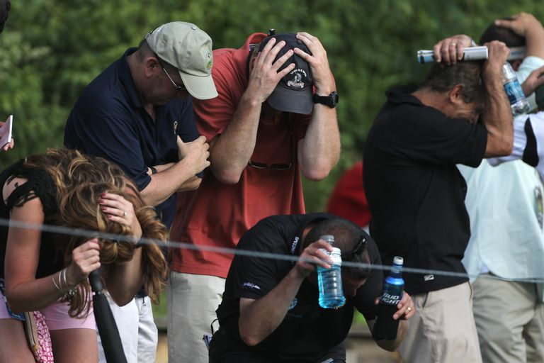 Spectators take cover as a wayward shot heads into the crowd during The Travelers Championship
