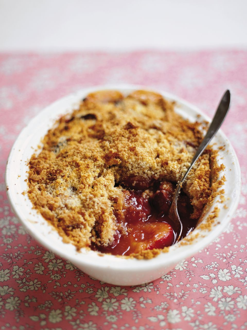 Bowl of plum crumble with spoon embedded, high angle view