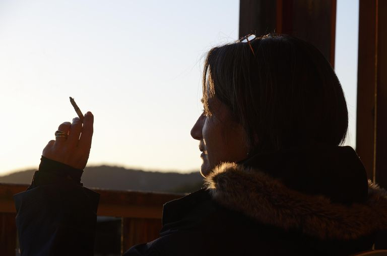 A woman holding a cigarette, outdoors at sunset