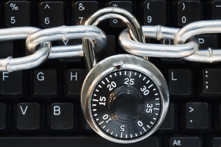 Photo of a combination lock and chain on a computer keyboard