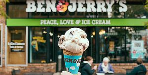 An ice cream cone held up in front of Ben & Jerry's.
