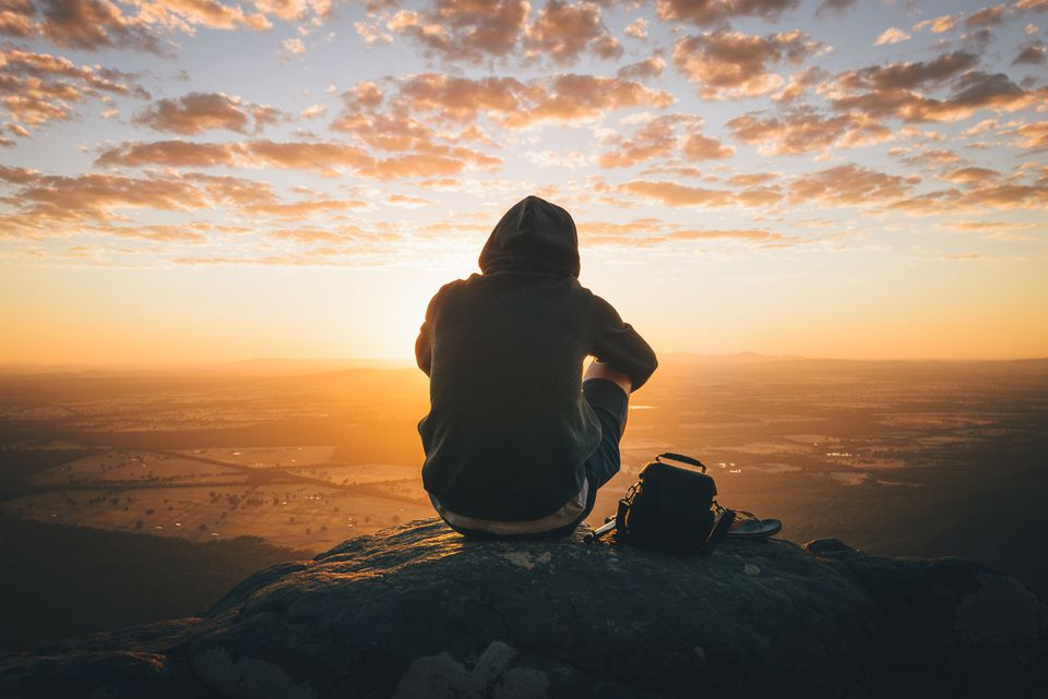man sitting on mountain in Australia after hike
