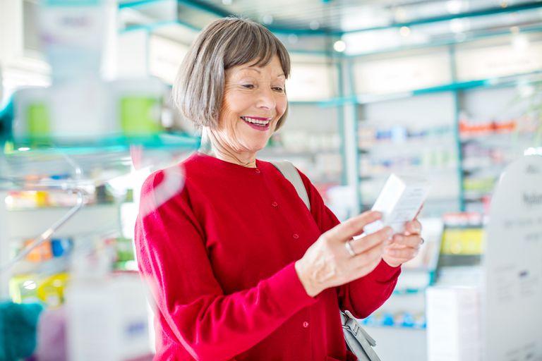 Smiling senior woman buying medicine