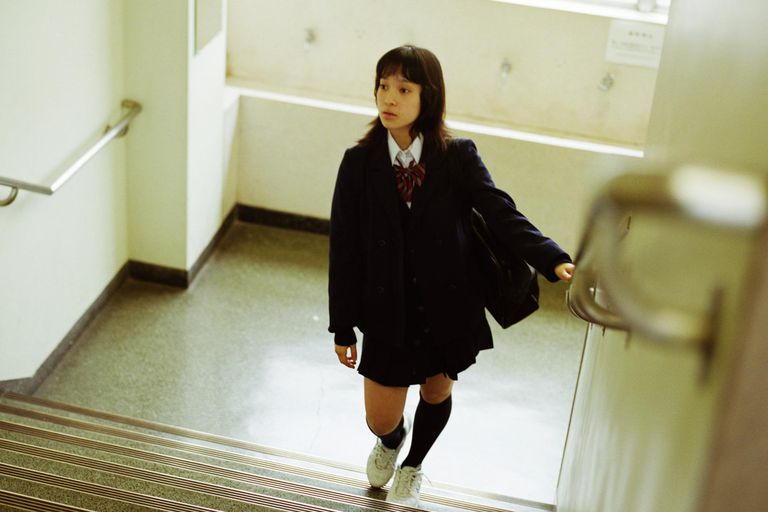 School girl (12-14) walking up steps in school, elevated view