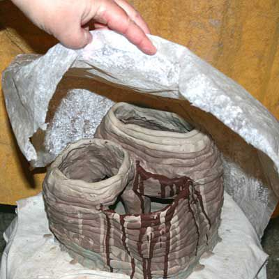 Cover the coiled pot with plastic to slow the drying down. This reduces problems with cracking.