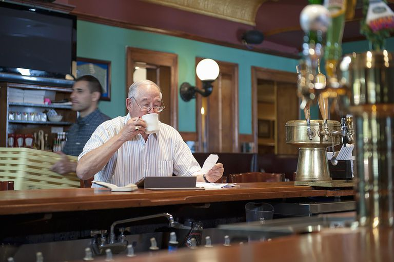 older man looking at receipts in cafe