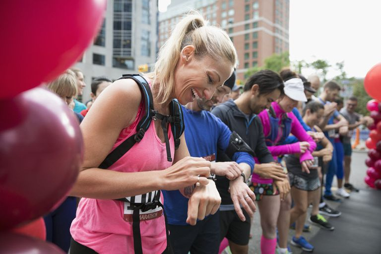 Runners at the start of a marathon, adjusting their fitness trackers.