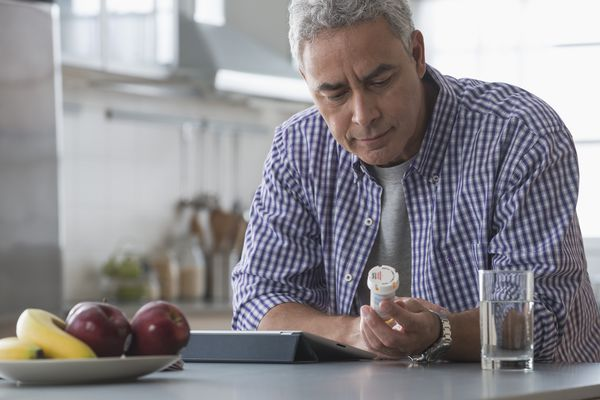 Hispanic man examining prescription bottle in kitchen
