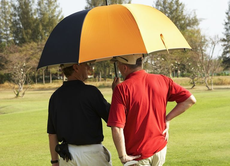 Two golfers standing under an umbrella