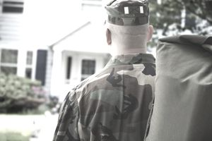 discharged soldier with bag standing in front of house