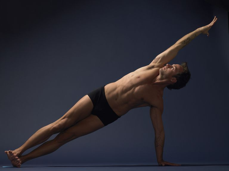 Man doing side plank pose (Vasisthasana)