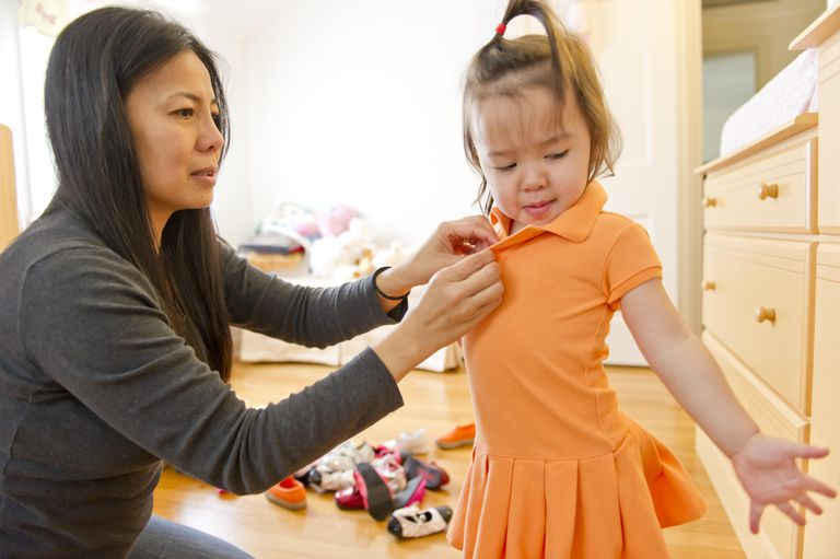 Asian mom dressing her toddler girl in a new dress
